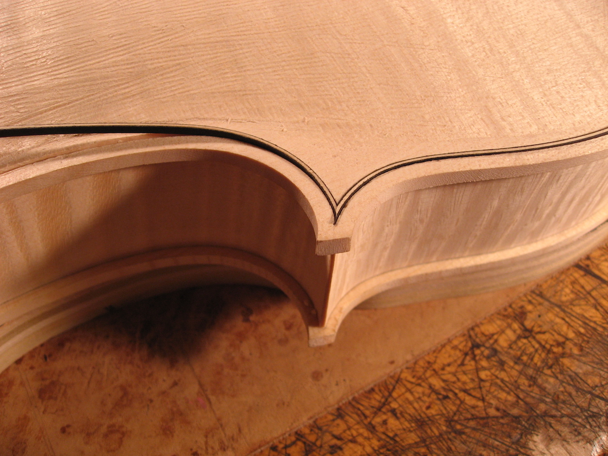 The purfling is inlaid with a precise miter at each corner